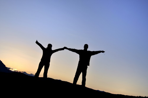 The shadow outline of a man and woman standing with arms outstretched on a mountain top at sunrise.
