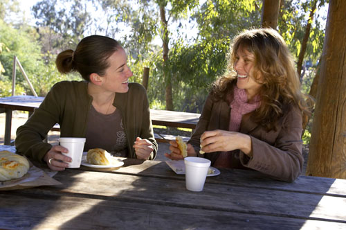 Two adult women talk while eating seated lunch at a picnic table in a park setting.