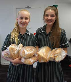 School girls holding loaves of bread